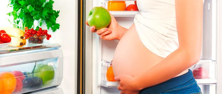 Schwangere Frau am Kühlschrank.